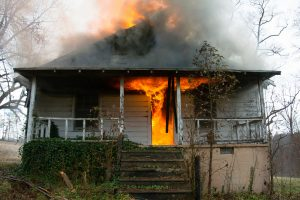 flames rolling out onto the porch of house on fire